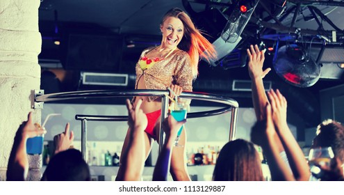 Adult woman dancer gogo dancing in a night club on stage