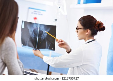 Adult woman discussing x-ray results during visit at female doctor's office