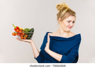 Adult woman do not like to eat vegetables, healthy food, vegetarian products. Female holding small shopping basket with green red vegetables, negative displeased face expression, on grey