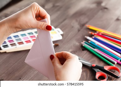 adult woman do origami boat from paper sheet
