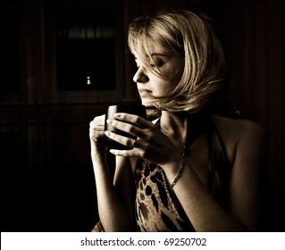 Adult woman drinking coffee in dark room beauty portrait