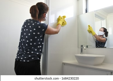 Adult woman with face mask and working rubber gloves cleaning and sanitizing home bathroom using disinfectant bleach cleaner to kill and prevent coronavirus spread. Real people. Copy space.