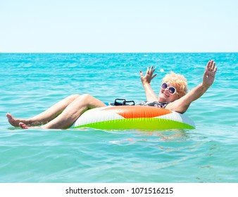 Adult woman floating in a rubber ring in the sea.