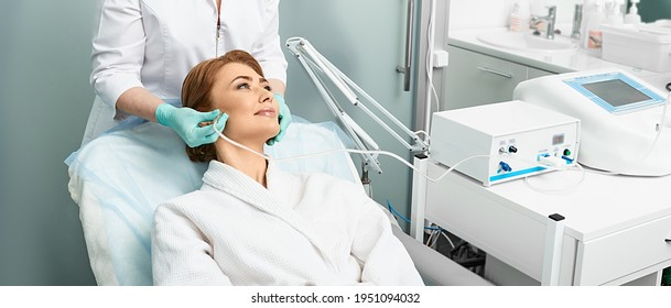 Adult woman getting rejuvenation skin face with ozone therapy procedure at beauty clinic using oxygen skin care machine