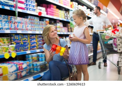 Adult woman and girl picking yogurt together in dairy section in groceries