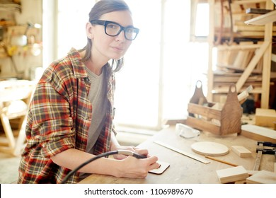 Adult woman in glasses using nice pyrography burner and looking at camera while sitting at workbench in carpenter workshop.