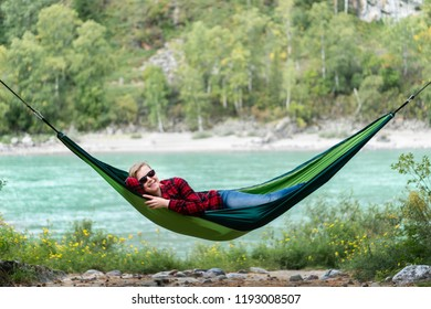 Adult woman in a hammock in the forest near river