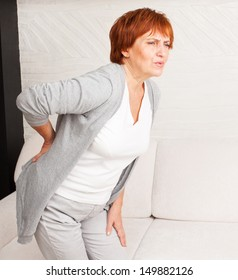 Adult woman has a backache. Mature female has pain in back