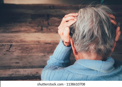 Adult woman has a headache. She sitting head in hands on dark black room. Concept dramatic loneliness, sadness, depression, sad emotions, cry, disappointed,healthcare, pain.