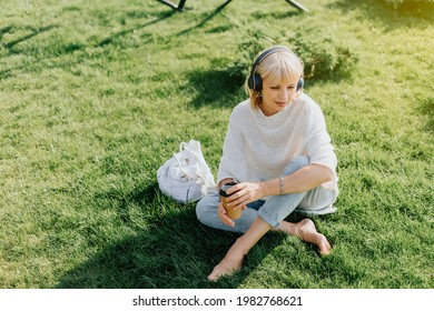 Adult Woman in headphones sitting on green grass outside in summer park at sunset. Happy and smiling senior listening music and drinking coffee in paper cup. Relax and meditation.