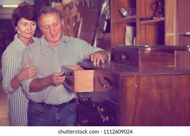 adult woman with her husband are buying antique curbstone for home in store