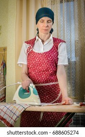 An adult woman, a housewife or a maid, with a green scarf on the head and wearing a red apron, is standing behind the ironing board. She irons some tea towels in the kitchen