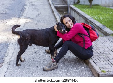 Adult woman hugging a big black stray dog and smiling