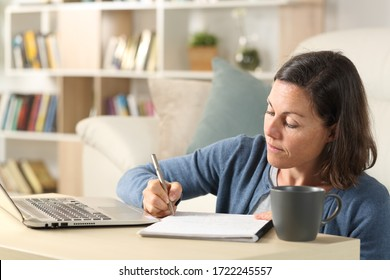 Adult woman with laptop writing notes on notebook sitting on the floor on a coffee table at home