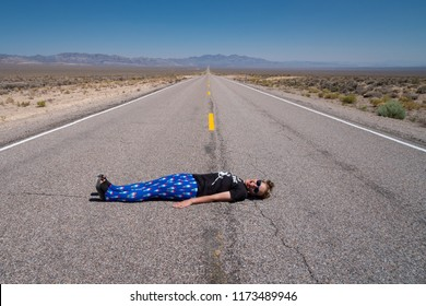 Adult woman lays down in the middle of the road (Extraterrestrial Highway in Nevada's desert). Concept for daring, daredevil, dare, open road