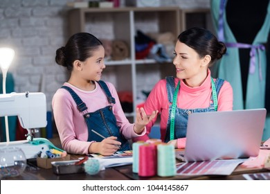 Adult woman and a little girl are choosing a color for clothing together. They are with mom in the sewing workshop in the evening.