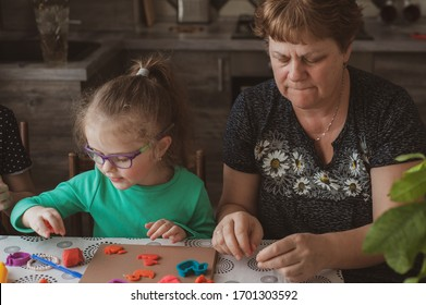 An adult woman and a little girl in glasses make figures from plasticine at home. Grandmother and granddaughter are sitting at home. Family Values Concept