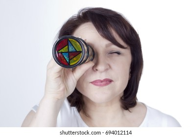 Adult woman looking into a kaleidoscope on a white background