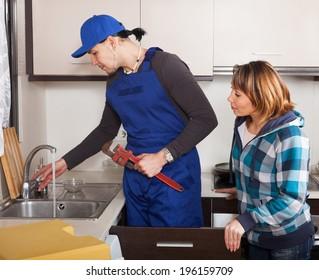 Adult woman looking as worker repairing  water lines
