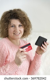adult woman makes a purchase from your mobile phone by credit card