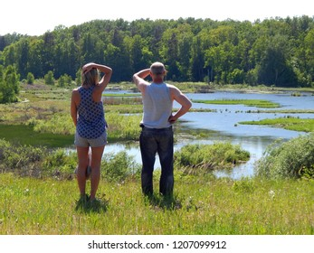 Adult woman and man admiring beautiful view of wild wetlands on sunny spring day, Masuria, Poland