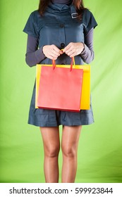 adult woman with miniskirt dress holding red and yellow shopping bags with green background