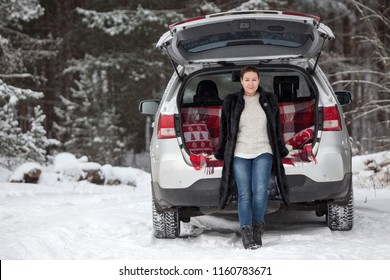 Adult woman in mink fur coat sitting in trunk of her car under opened back door, wintry forest