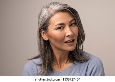Adult Woman of Mongolian Nationality with Gray Hair on a Gray Background. Her Gaze Looks Pensive. The Mouth of a Woman is Ajar. Mongolian Beauty Concept. Close Up Shoot.