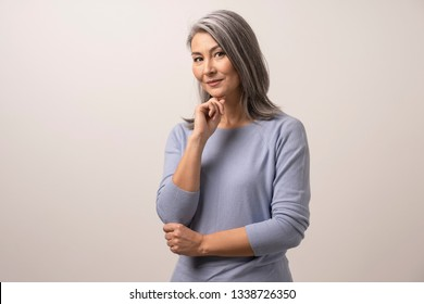 Adult Woman of Mongolian Nationality on a White Background. The Woman has Big Brown Eyes and Gray Hair. She is Wearing a Soft Blue Blouse. Mongolian Beauty Concept. Close Up Shoot.