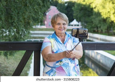 Adult woman with monopod taking selfie