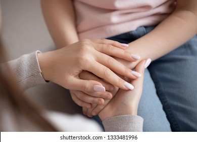 Adult woman mother holding hands of little child daughter love charity support concept, parent children protection, kid adoption, foster care, family trust connection hope and donation, close up view