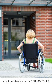adult woman on wheelchair entering the building - view from back