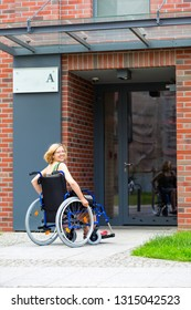 adult woman on wheelchair entering the building and looking back - view from back