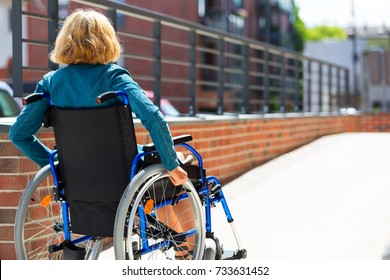 adult woman on wheelchair entering the platform or driveway - view from back
