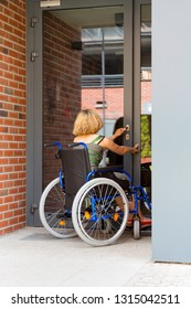 adult woman on wheelchair opening the door and entering the building - view from back