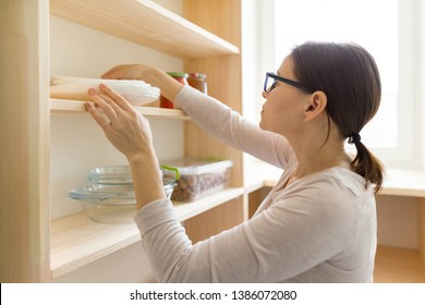 Adult woman picking food from storage cabinet in kitchen, storage with wooden shelves.