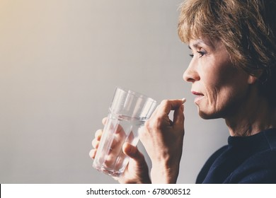 Adult woman with a pill and a glass of water / healthcare concept