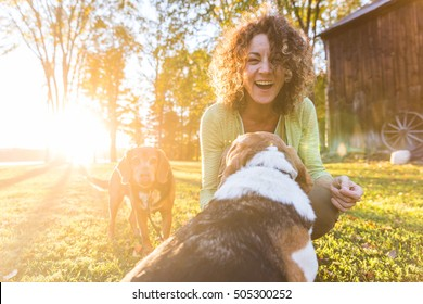 Adult woman playing with her dogs at park or in the backyard. Autumn colors, unstaged situation with candid model and playful dogs. Lifestyle and friendship concepts.