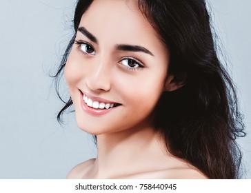 Adult woman portrait, skin care concept, beautiful skin over gray background. Studio shot.