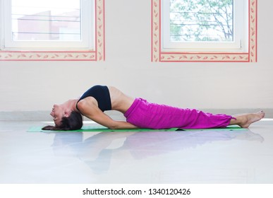 adult  woman practice yoga indoor fish pose full body shot natural light