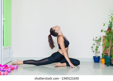 adult  woman practice yoga pigeon pose  indoor full body shot natural light