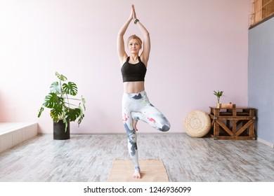 Adult woman practicing yoga Tree pose Vrikshasana asana indoors, doing yoga and pilates exercise.