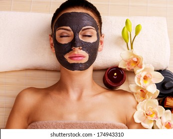 Adult woman relaxing in spa salon. Female face with cosmetic mask. Beauty treatment