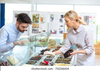 adult woman selling chocolates with praline and other fillings