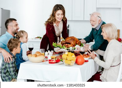 adult woman and senior man carrying baked turkey for thanksgiving dinner with family