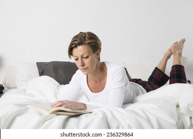 Adult woman with short hair reading a book in bed