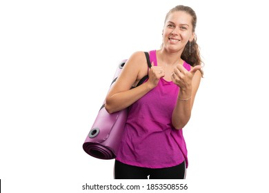 Adult woman showing friendly smile in pink sports tanktop holding yoga mat making like gesture using thumb-up with blank copyspace for advertising isolated on white background