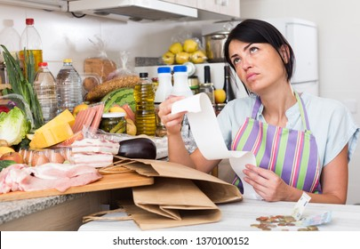 Adult woman is sitting with check and is sading because of the prices of food at home.