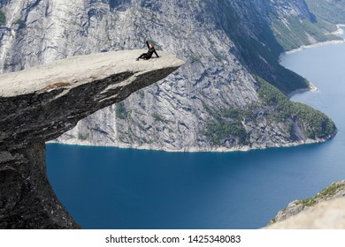 Adult woman sitting on Trolltunga rock formation and waving hand. Jutting cliff is in the Odda, Hordaland county, Norway
