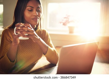 Adult woman smiling sitting near bright window while looking at open laptop computer on table and holding white mug